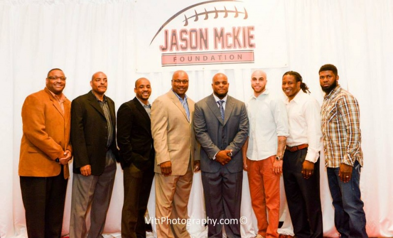 Jason poses with family and players